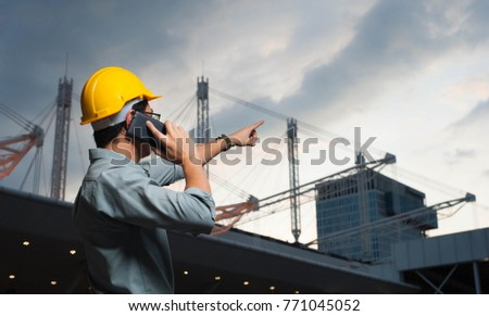 Engineer is pointing the job,Engineer  is setting goal,Engineer is controlling the construction on twilight background,Engineer using a mobile phone to contact the job