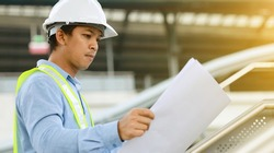 engineer look at blueprint draft paper at construction site