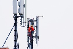 Engineer maintenance on telecommunication tower doing ordinary maintenance and control to an antenna for communication, 3G, 4G and 5G cellular. Cell Site Base Station.