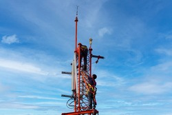 Engineer maintenance on telecommunication tower doing ordinary maintenance and control to antenna for communication, 3G, 4G and 5G cellular. Cell Site Base Station on blu sky background.