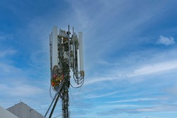 Engineer maintenance on telecommunication tower doing ordinary maintenance and control to antenna for communication, 4G and 5G cellular. Cell Site Base Station on blu sky background.