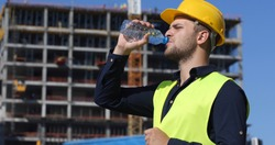 Engineer Man Drink Water in a Hot Summer Day,  Worker Male Have a Break near Under Construction Building