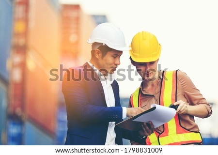 Engineer man, Foreman manager,in hardhat with Female foreman worker working in the construction container yard, Industrial Container yard for Logistics oversea import export shipping business.  ストックフォト ©