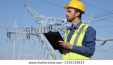 Engineer Man Taking Notes on Clipboard Looking Out at Electric Pillar Powerline Infrastructure #1145134814