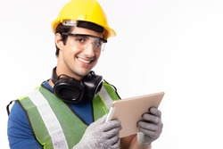Engineer man working on digital tablet computer at worksite. Handsome young industrial worker wear hardhat, safety glove, safety glasses, headphones with smiley face, happy. Worker guy get successful