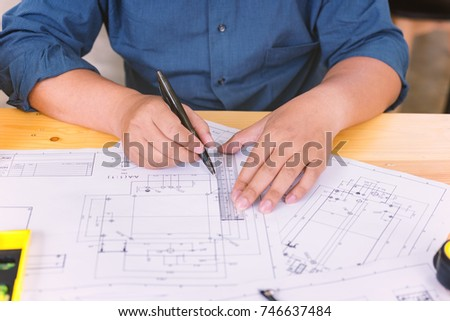 Engineer man working with drawings inspection in workplace in office .Engineering tools and construction concept. architect and Business concept. #746637484