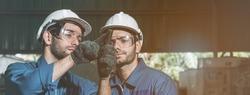 Engineer men wearing uniform safety workers perform maintenance in factory working machine lathe metal.