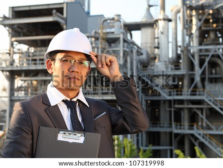 engineer oil refinery holding a notepad