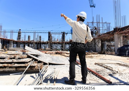 Engineer on construction site with blue sky background.