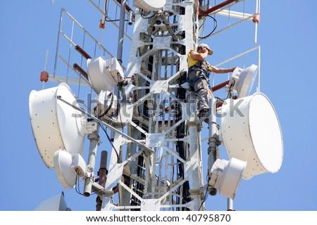 Engineer on phone on top of telecom pylon