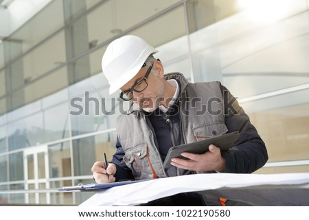 Engineer on site checking project on digital tablet