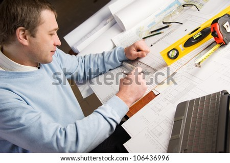 Engineer or architect in blue pullover is working on construction plans.
