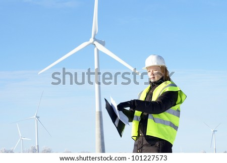 engineer or architect with white safety hat and wind turbines on background