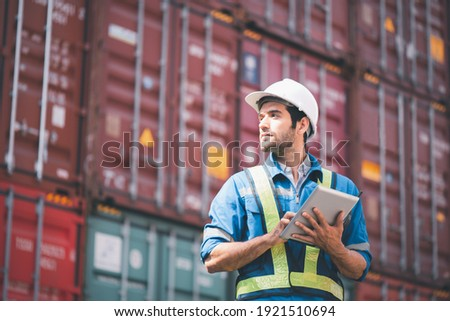 Engineer or foreman holding tablet and wears PPE looking at left side to checking inventory or job details with cargo container background. Engineering site and working with technology concept. Photo stock ©