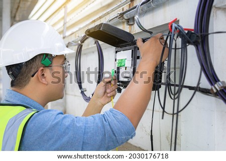 Engineer or technician checking fiber optic cables in internet splitter box.Fiber to the home equipment. FTTH internet fiber optics cables and cabinet. Foto stock ©