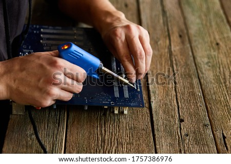 Engineer or technician repair electronic circuit board with soldering iron. Man hands soldiers computer circuit board using soldering iron. Copy space. Photo stock ©