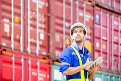 Engineer or Technician wears white hardhat and reflection shirt and holding tablet and look at sky and smile with cargo stacked containers in background. Concept of inventory and logistic management.