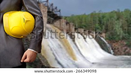 engineer or worker hand hold yellow helmet for workers security over Background to dam bridge weir in perspective Idea of power energy electricity Empty Copy space for inscription