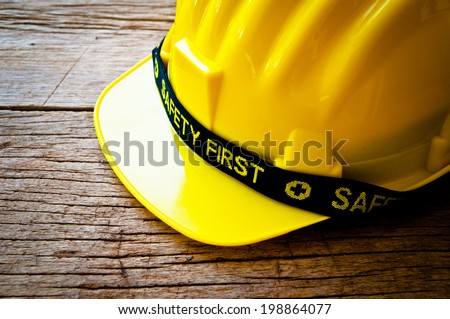 Engineer or Worker Yellow Safety Helmet Hat with SAFETY FIRST word tag on Wood background Rustic Style Concept for Carpentry Carpenter Work