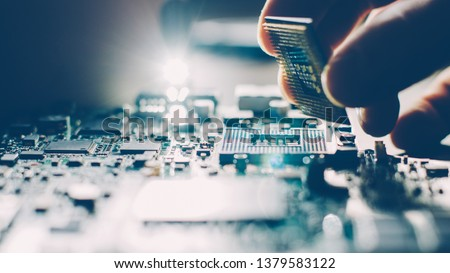 Engineer plugging CPU microprocessor to motherboard socket. Computer technology and hardware maintenance or repair. #1379583122