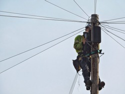 Engineer repairing cables on telegraphic pole