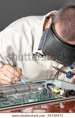 Engineer repairing circuit board, in computer equipment. coarse style picture - stock photo