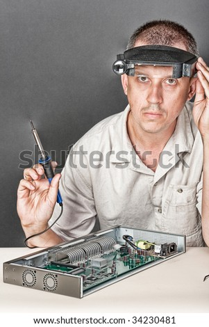 Engineer repairing circuit board, in computer equipment. coarse style picture