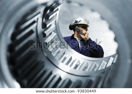 engineer, seen through the shaft of giant gear wheel, machine engineering idea