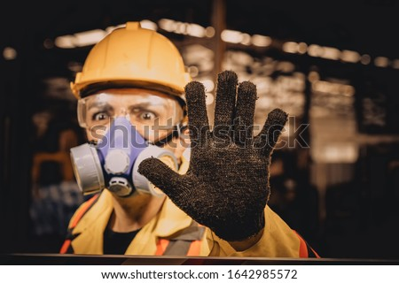 Engineer show hand for stop and wearing a gas mask on his face working in industrial factory.worker engineer industry.engineer workplace in industrial company with mechanical engineering.