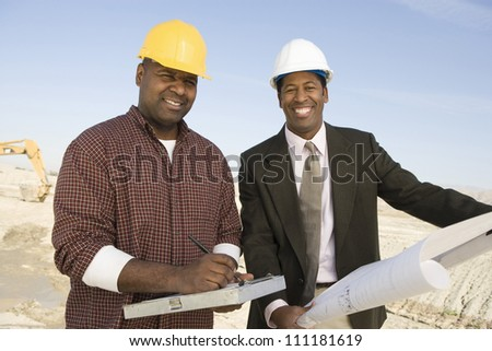Engineer showing blueprint for a worker at construction site
