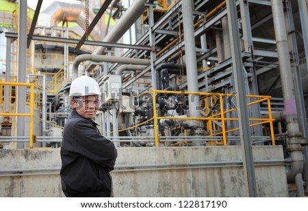 engineer standing beside pipeline inside oil refinery