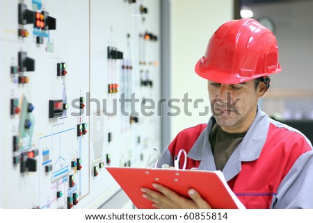 Engineer standing in front of the control panel in the control room and write the results of the measurements. - stock photo