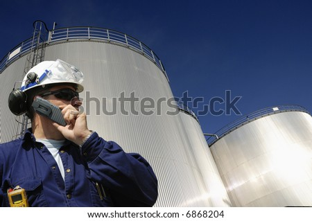 engineer talking in mobile-phone in front of refinery oil tanks