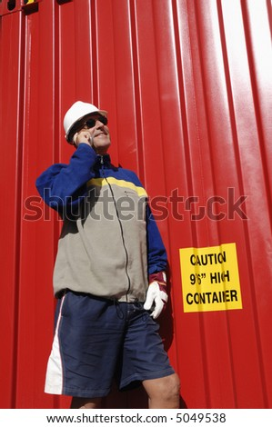 engineer talking in mobile-phone inside container-port, red container in background