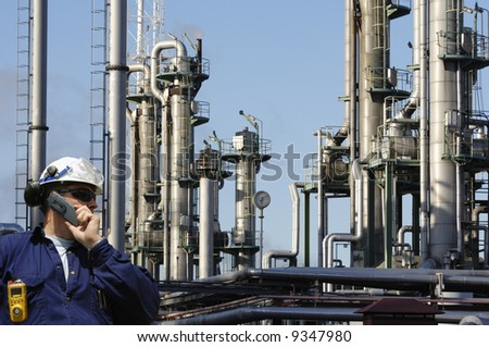 engineer talking in phone in front of large oil and gas refinery