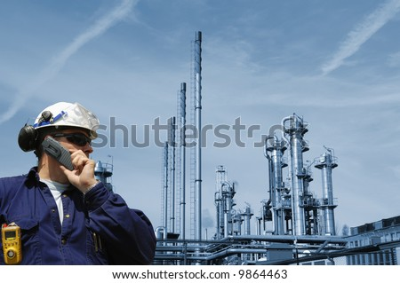 engineer talking in phone with a large blue toned oil and gas refinery in background
