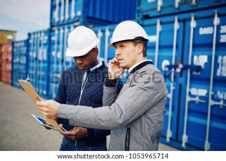 Engineer talking on a cellphone and reading an inventory list on a clipboard while standing with a colleague in a commercial shipping yard