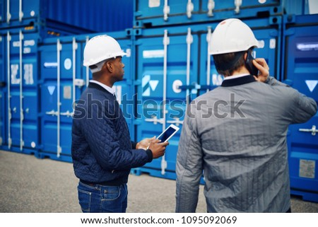 Engineer talking on a cellphone while standing in a shipping yard with a colleague reading an inventory list on a digital tablet