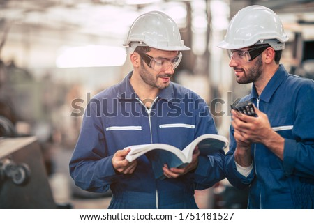 Engineer team talking together teach and learn engineering technical about using machine with open instruction manual text book in factory workplace. ストックフォト ©