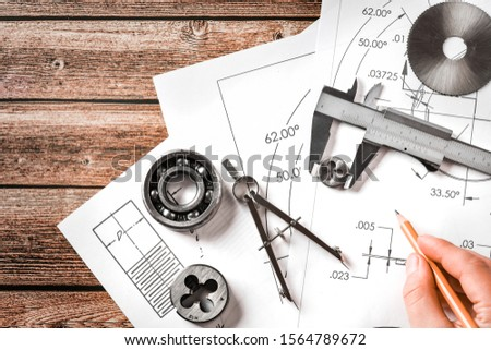 Engineer technicial drawings and mechanical parts engineering industry work project paper prints. Projectant hand with pencil, measuring tools on table.