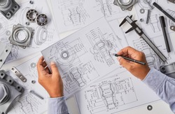 Engineer technician designing drawings mechanical parts engineering Engine manufacturing factory Industry Industrial work project blueprints measuring bearings caliper tools