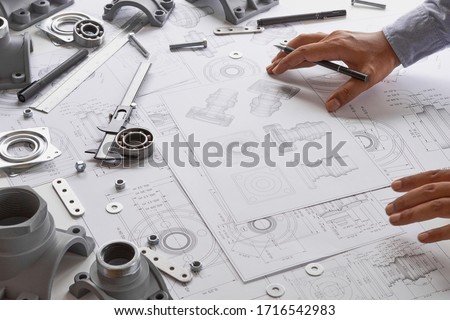 Engineer technician designing drawings mechanicalparts engineering Engine manufacturing factory Industry Industrial work project blueprints measuring bearings caliper tool. ストックフォト ©