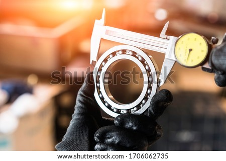 Engineer technician measure a ball bearing with vernier caliper, engineering Engine manufacturing factory Industry. Industrial Concept  Сток-фото ©