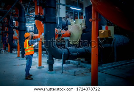 Engineer under checking the industry cooling tower air conditioner is water cooling tower air chiller HVAC of large industrial building to control air system.