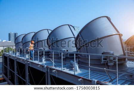 Engineer under checking the industry cooling tower air conditioner is water cooling tower air chiller HVAC of large industrial building to control air system. Stock photo ©
