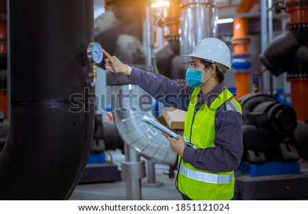 Engineer under checking the industry cooling tower air conditioner is water cooling tower air chiller HVAC of large industrial building to control air system ,wearing mask for protect pollution.