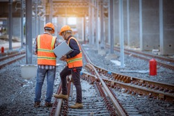 Engineer under discussion inspection and checking construction process railway switch and checking work on railroad station .Engineer wearing safety uniform and safety helmet in work.