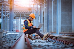 Engineer under inspection and checking construction process railway switch and checking work on railroad station by notebook .Engineer wearing safety uniform and safety helmet in work.