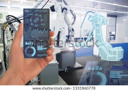Engineer uses a futuristic transparent smartphone to control robots in a smart factory. Smart industry 4.0 concept.