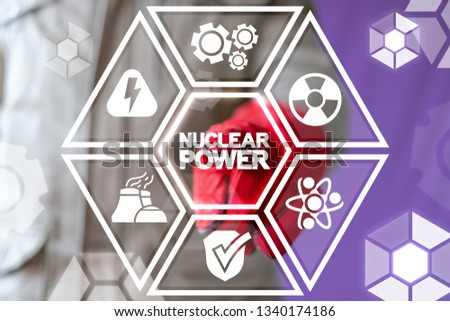 Engineer uses on a virtual screen of the future and touches the inscription: nuclear power. Nuclear power plant concept. Generation ecology atomic energy modern factory. Safety atom.